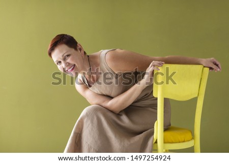 Woman with short hair sitting on chair #1497254924