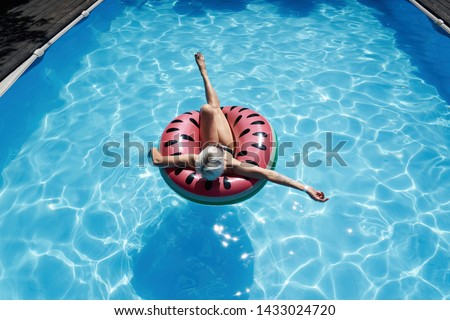 Woman with short hair swimming relaxing in a pool with pink floatie Inflatable doughnut, blue water, chill, tanning under sun.                        #1433024720