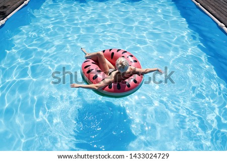 Woman with short hair swimming relaxing in a pool with pink floatie Inflatable doughnut, blue water, chill, tanning under sun.  #1433024729