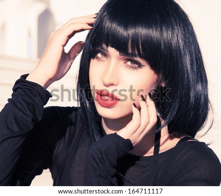 Woman with short stylish hairstyle and pink make up.Exotic woman beauty. Black shine hair . Hairdresser. Female . Retro style . Sexy look . Pink lips.