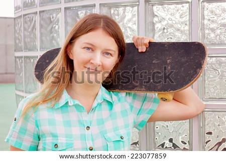 Woman with skateboard wearing plaid shirt