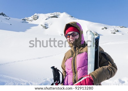 Woman with skies in hand in front of a hill at alps mountains