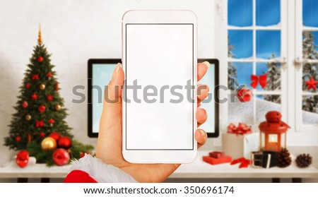 Woman with smart phone in hands in Christmas time. Device with white screen for mockup. Christmas tree, gifts, decorations in background.