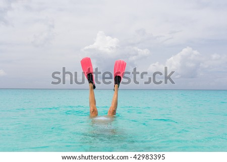 woman with snorkel fins diving in turquoise island water - stock photo