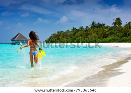 Woman with snorkeling gear running into the turquoise, tropical waters of the Maldives #795063646