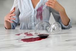 Woman with spilled glass of wine and stain on her shirt at table indoors, closeup