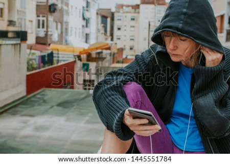 woman with sportswear and mobile phone with headphones in the city