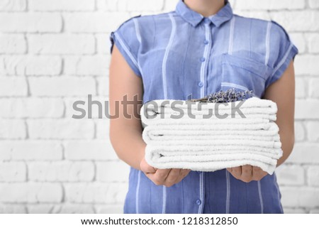 Woman with stack of clean towels against white brick wall #1218312850
