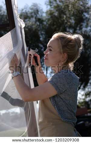 Woman with stapler hanging curtain on courtyard. Female designer decorating the wedding arch outdoors, preparation for the holiday