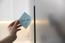 Woman with sticky note saying I Love You near fridge door, closeup. Romantic message