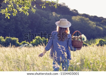 Woman with straw hat is holding wicker basket and standing in meadow. Elderberry harvest. Tranquility scenery with woman in sunlight.