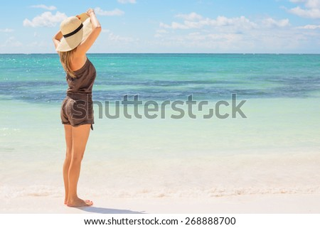Woman with straw hat standing on the beach #268888700