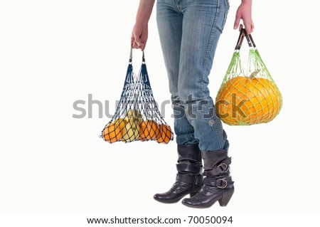 Woman with string shopping bags (Einkaufsnetz) carrying different yellow fruits