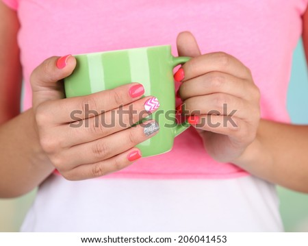 Woman with stylish colorful nails holding mug, close-up, on color background