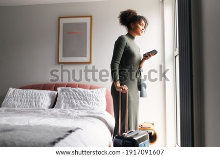 Woman with suitcase checking out of boutique hotel standing by bed waiting for taxi ordered on mobile phone app Сток-фото ©
