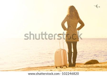 woman with suitcase is traveling at sea coast in winter