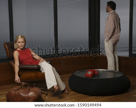 Woman with suitcase looking away from boyfriend
