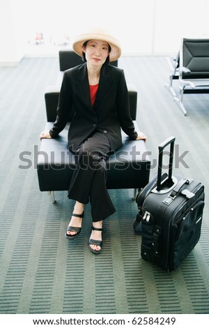 Woman with suitcase sitting at airport