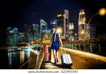 Woman with suitcases on the Jubilee bridge in Singapore at night #622491041