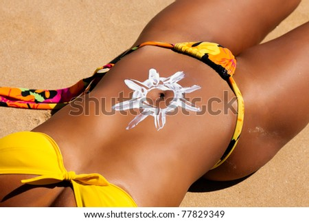 Woman with suncream on the belly at the beach in summer