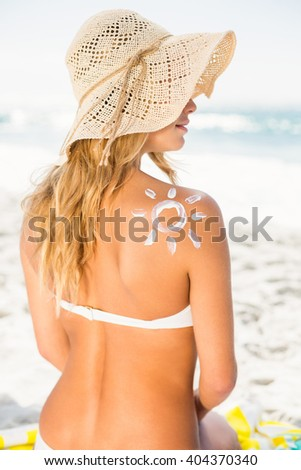 Woman with sunscreen on her skin on a sunny day #404370340