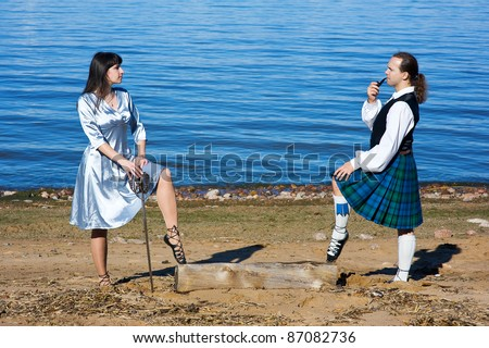 Woman with sword and man in scottish costume with pipe near the sea