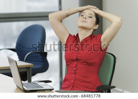 Woman with the red shirt in the office with a laptop while resting