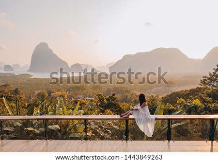 Woman with the white dress sit and see the mountain in early morning at the Sametnangshe Island viewpoint, Phang-Nga, Thailand. #1443849263