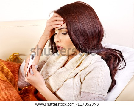 Woman with thermometer having  flue in bed. Indoors.