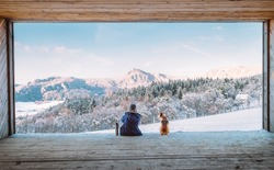 Woman with thermos flask sitting with her beagle dog in the big wooden hangar with a huge panoramic window and looking on the snowy mountain landscape. Human and pets relatives concept image.