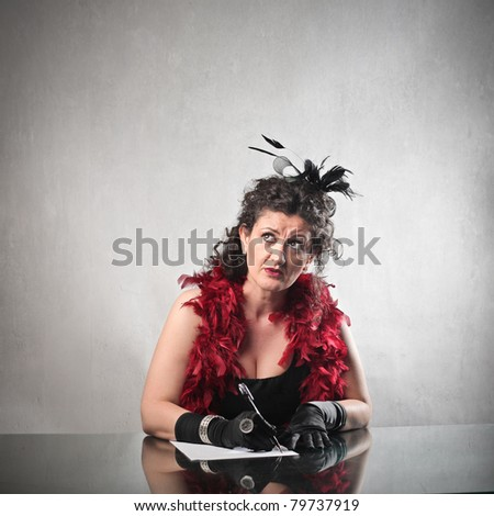 Woman with thoughtful expression writing a letter - stock photo