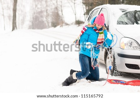 Woman with tire chains car snow breakdown winter problematic young
