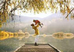 Woman with toddler on wooden pier bridge near by lake surrounded by branches of willow tree in autumn time. Mother and child together in countryside outdoors. Family in nature background.