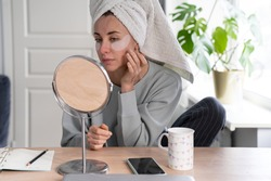 Woman with towel on head applying patches under eyes enriched with collagen, vitamin E, diminishes the signs of aging, helps reduse eye puffiness, looking in mirror. Face skin care beauty at home.