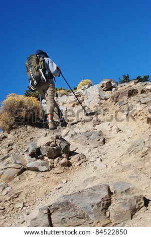 Woman with trekking poles and backpack hiking a rocky mountain