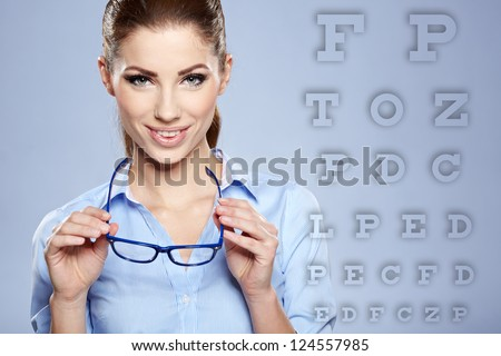 woman with  trendy glasses on the background of eye test chart