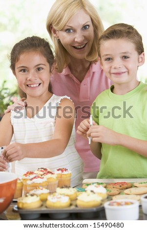 Woman with two children in kitchen decorating cookies smiling