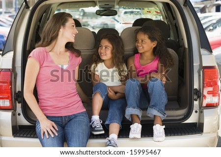 Woman with two young girls sitting in back of van smiling - stock photo