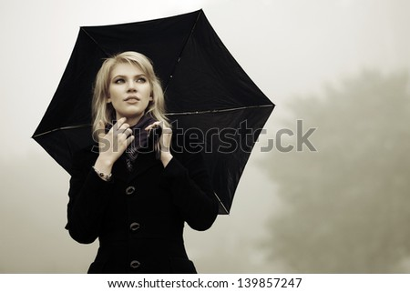 Woman with umbrella against a morning haze
