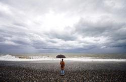 Woman with umbrella and backpack looking at stormy sea and overcast sky in Batumi, Georgia