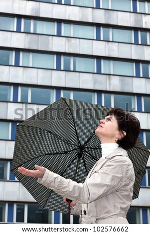 Woman with umbrella check whether it's raining