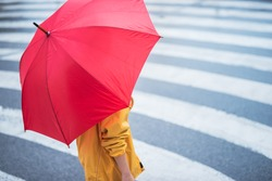 Woman with umbrella crossing the pedestrian. Selective focus on the hand.