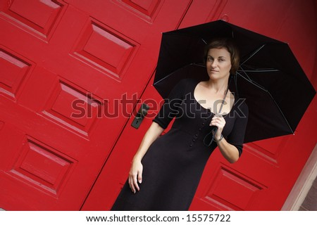 Woman with umbrella in front of red doors.