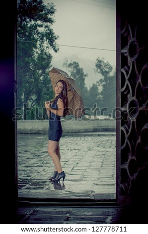Woman with umbrella in the rain vintage look