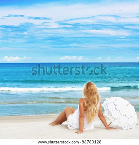 Woman with umbrella on the tropical beach
