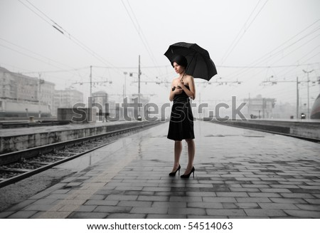 Woman with umbrella standing on the platform of a train station