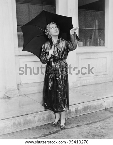 Woman with umbrella testing for rain