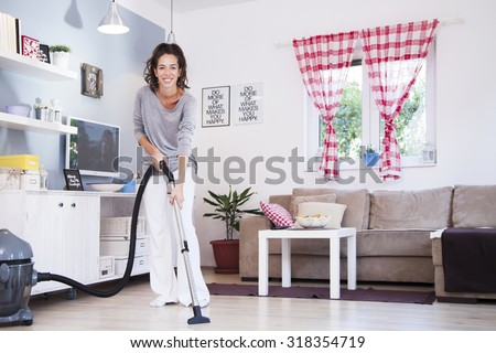 Woman with Vacuum Cleaner. Woman using vacuum cleaner at home in the living room