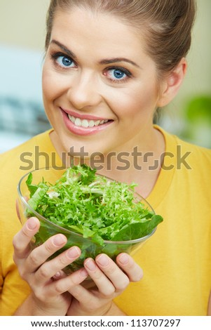 Woman with vegetarian food  standing against  home kitchen interior eating healthy food. Yellow color clothes. Close up woman face portrait.