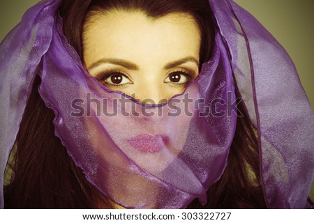 Woman with veiled face. Processed to look as if a vintage color photograph with mild cross processing.